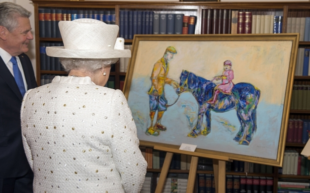 """Queen Elizabeth II is presented with a painting by Germany's Federal President Joachim Gauck at his official Berlin residence, Bellevue Palace, on the first full day of her state visit to Germany. The stylised painting of the Queen sat on a pony prompted the monarch to declare """"that's a funny colour for a horse"""" when the German president gave her the artwork. PRESS ASSOCIATION Photo. Picture date: Wednesday June 24, 2015. Artist Nicole Leidenfrost had painted a young Princess Elizabeth riding a blue coloured pony - which had flecks of yellow and green - with the Queen's father George VI also in the image holding the animal's reins. See PA story ROYAL Queen. Photo credit should read: Arthur Edwards/The Sun/PA Wire"""