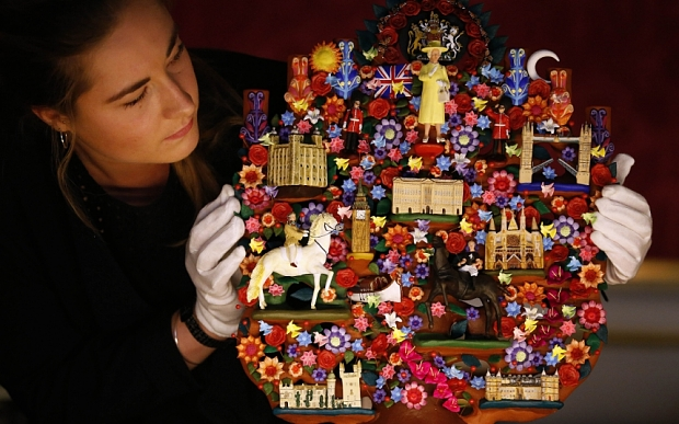 FILE- In this July 23, 2015 file photo, an employee of the Royal Collection Trust looks at the Tree of Life, a gift presented to Britain's Queen Elizabeth II from Mexican President Enrique Pena Nieto in 2015, during a press preview for the Summer opening of Buckingham Palace in London, A list of official gifts received by Queen Elizabeth II from world leaders and dignitaries during 2015 features jewelry, ornaments and some more unusual choices ? including homemade honey butter from Michelle Obama. (AP Photo/Frank Augstein, File)