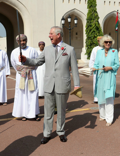 MUSCAT, MUSCAT - NOVEMBER 05: Prince Charles, Prince of Wales takes part in a traditional Omani 'Sword Dance' during a cultural welcome ceremony as Camilla, Duchess of Cornwall looks on ourside the Sultan's Palace on the second day of a Royal tour of Oman on November 5, 2016 in Muscat, Oman. Prince Charles, Prince of Wales and Camilla, Duchess of Cornwall are on a Royal tour of the Middle East starting with Oman, then the UAE and finally Bahrain. (Photo by Chris Jackson/Getty Images)